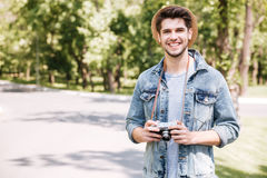 Glücklicher junger Mann im Hut mit alter Weinlesefotokamera Stockfotografie