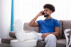 Glücklicher junger Mann mit dem gebrochenen Bein sprechend am Handy stockbilder