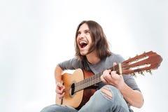 Glücklicher junger Mann mit dem langen Gitarre spielenden und singenden Haar Lizenzfreie Stockfotografie