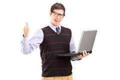 Glücklicher junger Mann mit dem Laptop, der sich Daumen zeigt Stockfotos