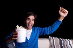 Glücklicher junger Mann, mit dem Popcornüberwachen Stockfotografie