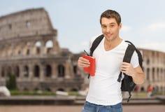 Glücklicher junger Mann mit dem Rucksack- und Buchreisen Stockfotos
