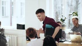 Glücklicher junger Mann mit Kastenwegen entlang dem multiethnischen Büro, das den Kollegen hohe fives nach Karriereerfolgsleistun stock footage