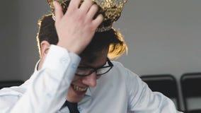 Glücklicher junger Mann mit Krone auf dem Kopf, der herum auf Stuhl im Büro einkreist stock video footage