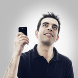 Glücklicher junger Mann mit Smartphone schaut oben Stockbild