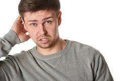 Glücklicher junger Mann mit unsicherem verwirrtem Ausdruck, auf grauem backg Lizenzfreie Stockfotos