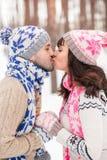 Glücklicher junger Mann und Frau, die im schneebedeckten Wald küsst Stockbilder