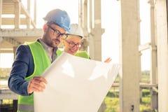 Glücklicher junger Mann und weibliche Architekten oder Teilhaber, die Grundrisse auf einer Baustelle betrachten lizenzfreie stockfotos