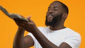 Glücklicher junger Manneswerfende Dollar um die Verschwendung des Geldes, Luxuslebensstil, Reichtum stock footage