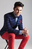 Glücklicher junger Modemann, der auf einem Schemel sitzt Lizenzfreies Stockfoto