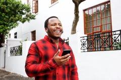 Glücklicher junger schwarzer Mann, der draußen mit Mobiltelefon geht stockbilder