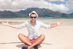 Glücklicher junger Sitzmann lädt Sie zum Strand ein Stockbild
