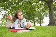 Glücklicher junger Student, der auf dem Grasstudieren liegt Lizenzfreie Stockfotos
