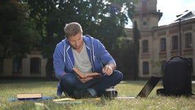 Glücklicher junger Student, der ein Buch im Park liest stock footage