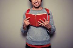 Glücklicher junger Student mit rotem Buch stockbilder