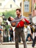 Glücklicher junger Vater, der mit seinem Sohn auf Hintergrund der Stadt spielt Stockbilder