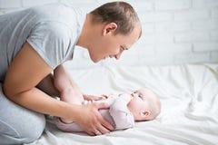 Glücklicher junger Vater, der zu Hause mit Baby spielt Lizenzfreie Stockbilder
