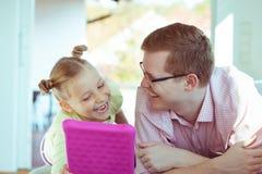 Glücklicher junger Vater haben Spaß mit seinem Arbeitsesprit der kleinen Tochter stockbild