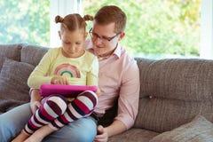 Glücklicher junger Vater haben Spaß mit seinem Arbeitsesprit der kleinen Tochter stockbilder