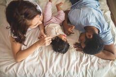 Glücklicher junger Vater, Mutter und nettes Baby, die auf dem Bett liegen lizenzfreie stockfotos