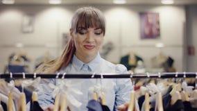 Glücklicher junger weiblicher Käufer nimmt viel Kleidung von einem Gestell, in einem Bekleidungsgeschäft und es zum passenden Rau stock video