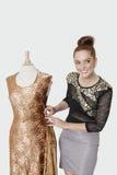 Glücklicher junger weiblicher Modedesigner, der an einer Ausstattung über grauem Hintergrund arbeitet stockfoto