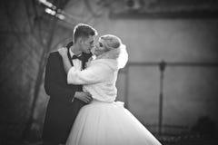 Glücklicher Jungvermähltenbräutigam, der blonde schöne Braut umarmt und küsst Stockbild