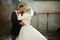 Glücklicher Jungvermähltenbräutigam, der blonde schöne Braut umarmt und küsst Lizenzfreie Stockfotos