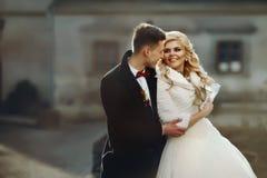 Glücklicher Jungvermähltenbräutigam, der blonde schöne Braut von hinten umarmt Stockfotos