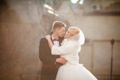 Glücklicher Jungvermähltenbräutigam, der herein blonde schöne Braut bei Sonnenuntergang umarmt Stockbild
