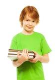 Intelligenter Junge mit Stapel der Bücher Stockfotografie