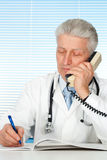 Glücklicher kaukasischer Doktor mit einem Telefonsitzen lizenzfreie stockfotografie