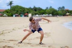 Glücklicher kaukasischer Mann, der auf werfenden Steinen des Strandes auf Ozean, Bali spielt lizenzfreies stockfoto