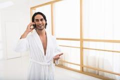 Glücklicher Kerl, der am Telefon in der Toilette in Verbindung steht Lizenzfreie Stockfotografie