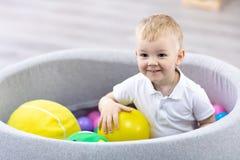 Glücklicher Kinderjunge, der den Spaß Innen in der Spielmitte hat Kind, das mit bunten B?llen im Spielplatzballpool spielt stockfotografie