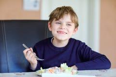 Glücklicher Kinderjunge, der frischen Salat mit Tomate, Gurke und unterschiedlichem Gemüse als Mahlzeit oder Imbiss isst Gesundes stockbild