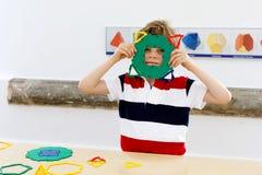 Glücklicher Kinderjunge, der Spaß mit Gebäude hat und geometrische Zahlen, Mathematik und Geometrie lernend schafft Lizenzfreies Stockfoto