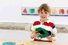 Glücklicher Kinderjunge, der Spaß mit Gebäude hat und geometrische Zahlen, Mathematik und Geometrie lernend schafft Stockfotografie