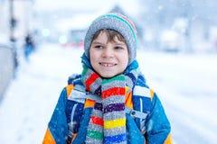 Glücklicher Kinderjunge, der Spaß mit Schnee auf Schulweg hat stockbild