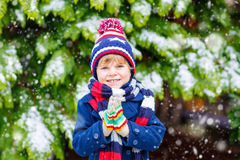 Glücklicher Kinderjunge, der Spaß mit Schnee im Winter hat Stockfotos