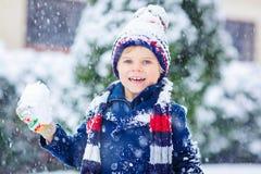 Glücklicher Kinderjunge, der Spaß mit Schnee im Winter hat Lizenzfreie Stockfotografie