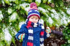 Glücklicher Kinderjunge, der Spaß mit Schnee im Winter hat Lizenzfreie Stockbilder