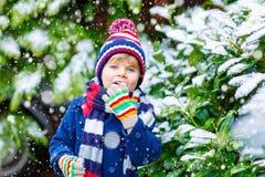 Glücklicher Kinderjunge, der Spaß mit Schnee im Winter hat Lizenzfreie Stockfotos