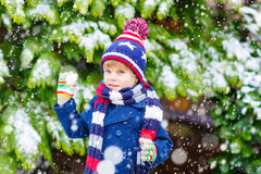 Glücklicher Kinderjunge, der Spaß mit Schnee im Winter hat Stockfotografie