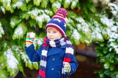 Glücklicher Kinderjunge, der Spaß mit Schnee im Winter hat Stockbilder