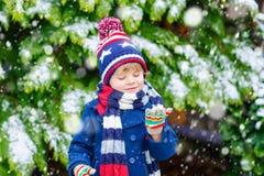 Glücklicher Kinderjunge, der Spaß mit Schnee im Winter hat Stockfoto