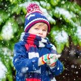Glücklicher Kinderjunge, der Spaß mit Schnee im Winter hat Stockbild