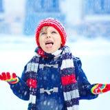 Glücklicher Kinderjunge, der Spaß mit Schnee im Winter hat lizenzfreies stockfoto