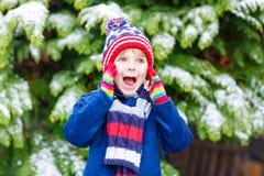 Glücklicher Kinderjunge, der Spaß mit Schnee im Winter hat Lizenzfreies Stockbild