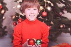 Glücklicher Kinderjunge, der Weihnachtsdekorationen hält Stockbild